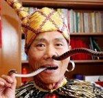 Китаец засовывает  змей в нос и вытаскивает изо рта